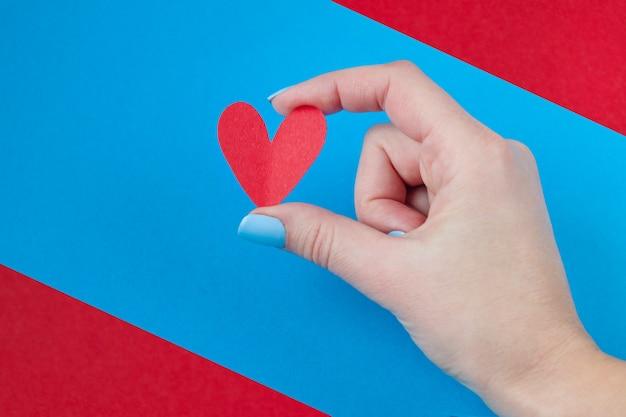 Entregue guardarar um coração vermelho em um fundo vermelho e azul. plano de fundo para o dia dos namorados