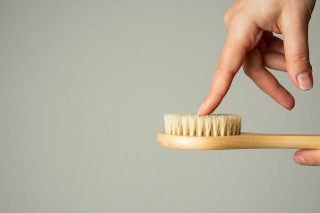Entregue manter a escova de madeira do banho do corpo isolada no fundo branco. zero desperdício, sem plástico. copie o espaço.