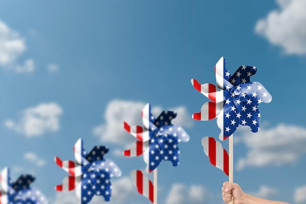 Entregue manter a turbina eólica patriótica dos eua sobre o fundo do céu azul.