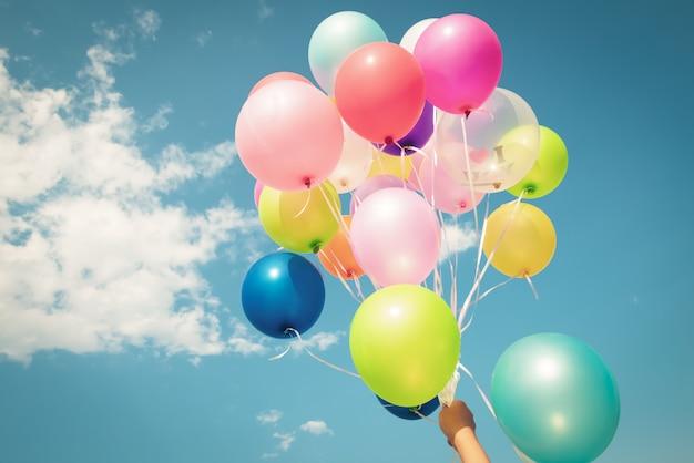Entregue manter multi balões coloridos feitos com um efeito retro do filtro do instagram do vintage.