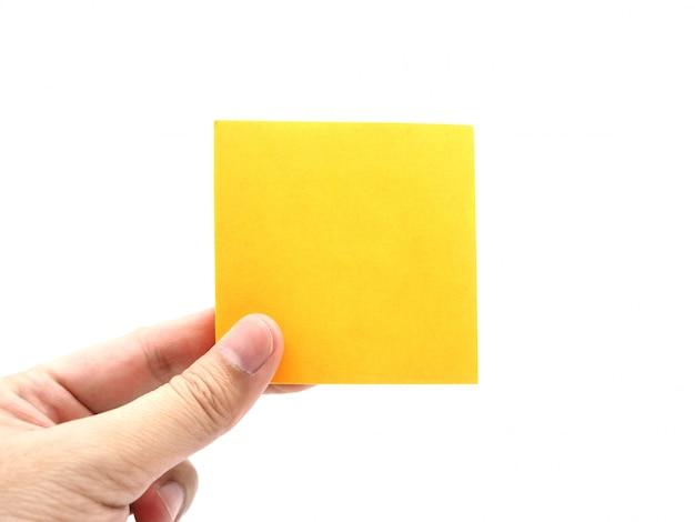 Entregue manter uma nota alaranjada da vara do papel isolada em um fundo branco.