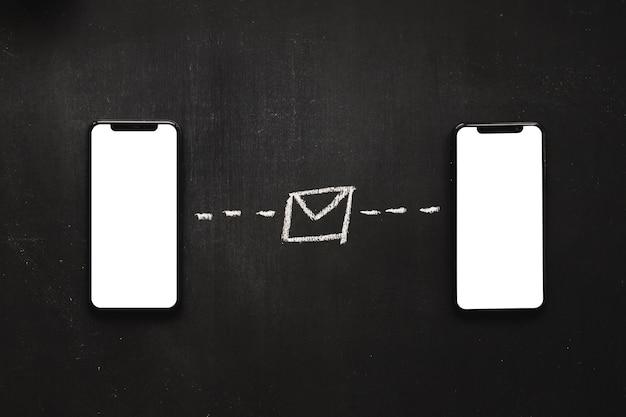 Entregue mensagens de texto desenhadas entre o dois telemóvel no quadro-negro