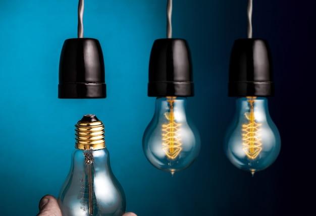 Entregue mudar lâmpadas antigas de um filamento do estilo de edison na obscuridade - fundo azul.