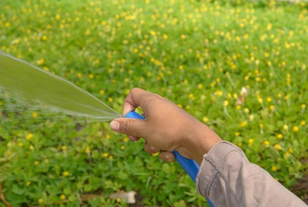 Entregue na água fresca de derramamento no vidro com o fundo verde da natureza.