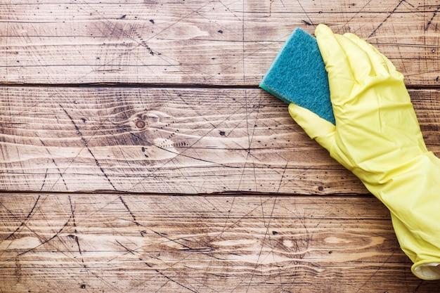 Entregue na esponja amarela da luva e da limpeza para limpar no fundo de madeira.