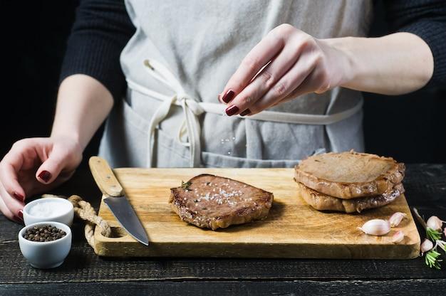 Entregue o bife salgado cozinheiro chefe em uma placa de desbastamento de madeira.