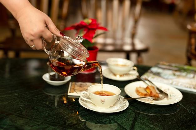 Entregue o chá de derramamento de um bule em um copo no fundo do borrão.