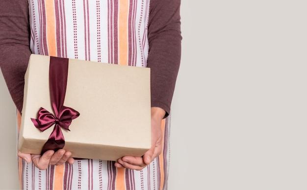 Entregue segurando a caixa de papel com fita cor de vinho no fundo branco.