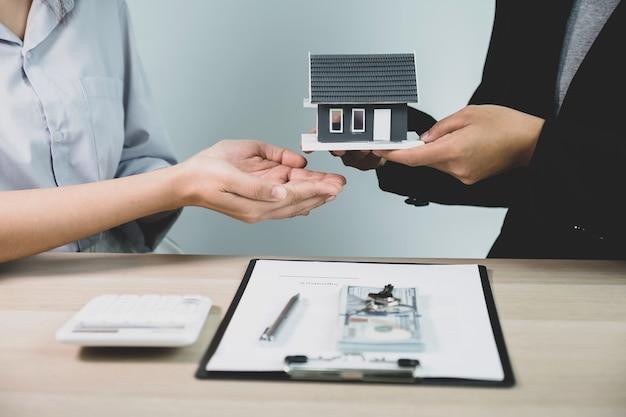 Entregue um corretor de imóveis, segure o modelo da casa e explique o contrato de negócios para a mulher compradora.