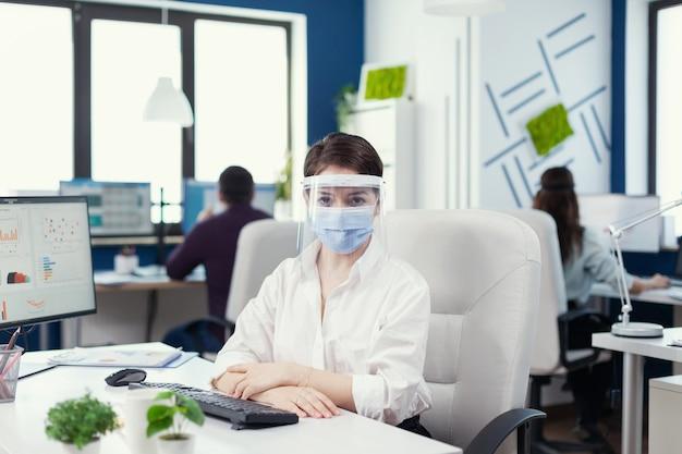 Entreneur usando máscara facial e vizor olhando para a câmera durante covid19. equipe empresarial atuando em empresa financeira respeitando a distância social durante pandemia global.