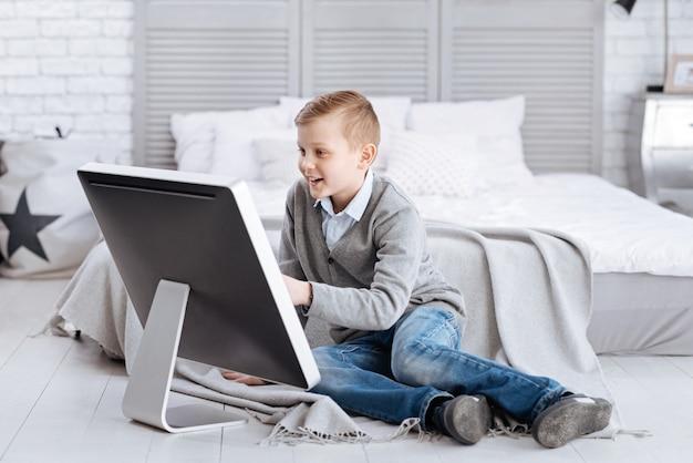 Entretenimento agradável. criança feliz feliz e positiva, sorrindo e sentada na frente da tela enquanto está em casa