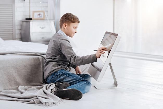 Entretenimento criativo. garoto inteligente positivo e feliz sentado em frente à tela digital e desenhando enquanto descansa em casa