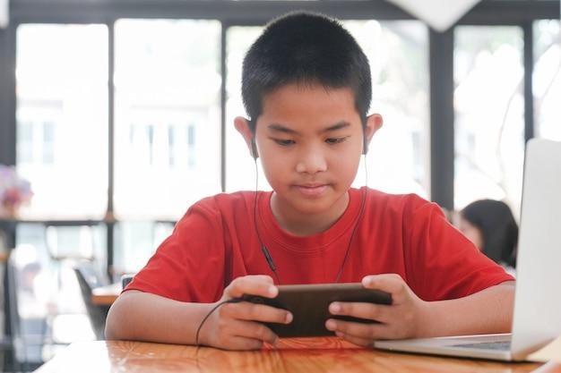 Entretenimento infantil e tecnologia. menino fofo feliz usando telefone celular e sorrindo, criança satisfeita jogando videogame no celular, conversando em rede social. interior
