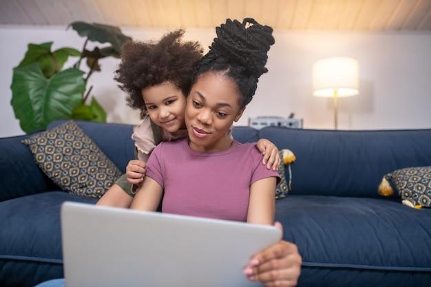 Entretenimento. mãe adulta jovem de pele escura sorridente com filhinha olhando para a tela do laptop em casa no quarto