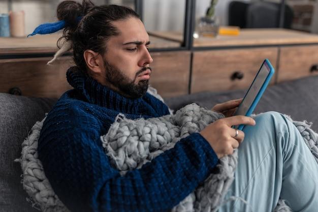 Entretenimento moderno. homem triste e desanimado usando seu tablet enquanto tenta se divertir