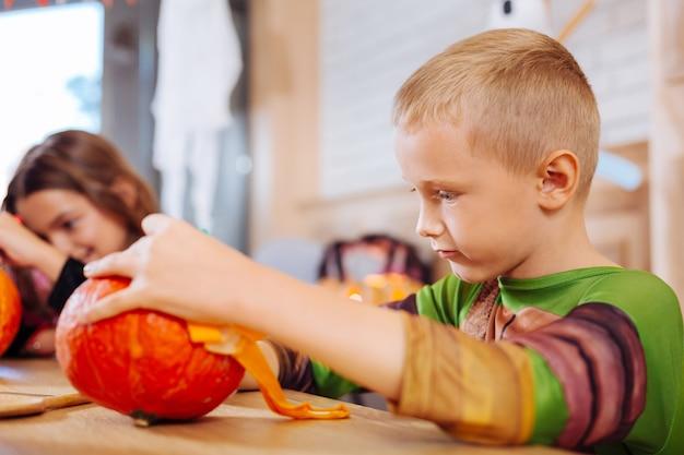 Entretenimento real. menino vestindo uma fantasia de tartaruga ninja se divertindo enquanto decora uma abóbora sentado à mesa