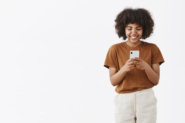 Entretido fofa feliz adolescente afro-americana com penteado afro em uma camiseta marrom segurando um smartphone e rindo de um vídeo engraçado na internet usando o dispositivo para se divertir