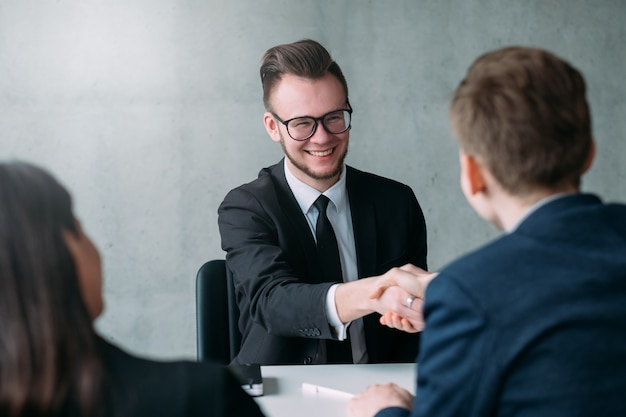 Entrevista de emprego bem-sucedida. carreira profissional. recursos humanos. jovem candidato do sexo masculino foi contratado para o cargo.