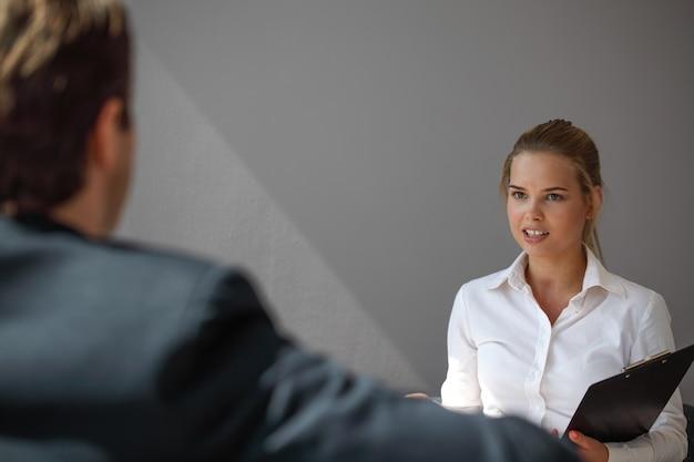 Entrevista de emprego - empresário ouve as respostas dos candidatos