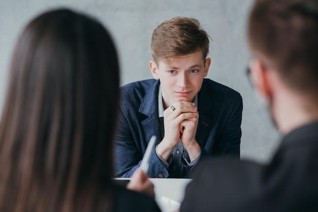 Entrevista de emprego estressante. carreira profissional. recursos humanos. jovem candidato do sexo masculino, nervoso, precisa conseguir o emprego.