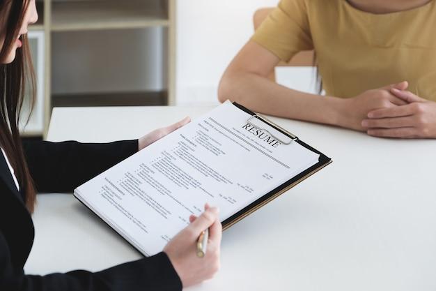 Entrevista de emprego no conceito de escritório, foco no currículo, empregador revendo o bom currículo do candidato qualificado preparado, recrutador considerando o aplicativo ou o gerente de rh tomando a decisão de contratação