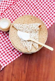Entrudo, panquecas com creme de leite em fundo de madeira. a vista do topo. o conceito de culinária, mardi gras