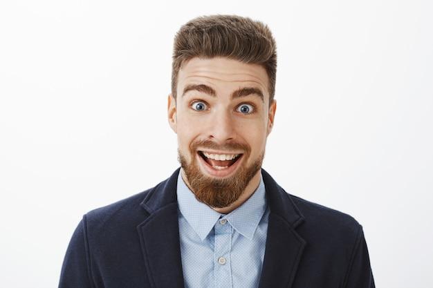 Entusiasmado, animado e surpreso, feliz homem bonito com barba e olhos azuis profundos, sorrindo amplamente com olhos arregalados de espanto encantado, sentindo-se impressionado e surpreso com as boas notícias
