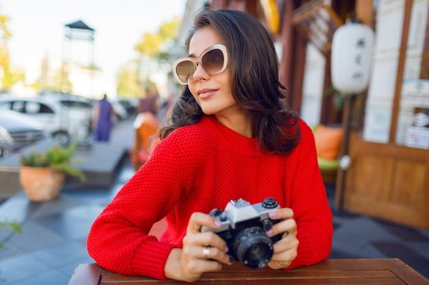 Entusiasmado cabelos longos mulher olhando para cima, tirando foto, apreciando a arquitetura incrível na velha cidade europeia. primavera ou outono. aconchegante camisola de malha vermelha. tempo ensolarado. cores quentes.