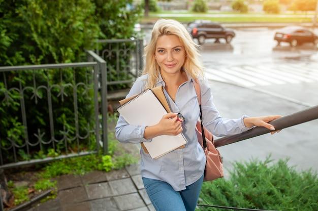 Entusiasmado feliz linda jovem sorrindo e segurando a pilha de livros s
