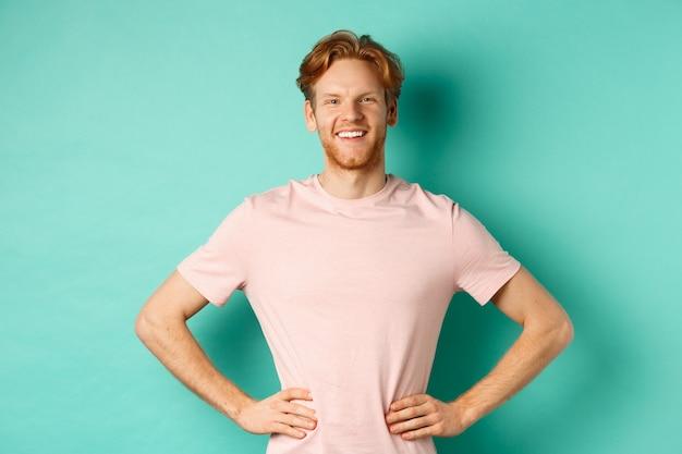 Entusiasmado jovem com cabelo ruivo, vestindo camiseta, feliz e orgulhoso de pé com as mãos no lúpulo, em pé sobre fundo turquesa.