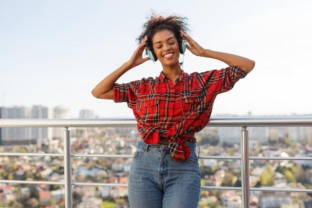 Entusiasmado mulher americana com pele escura, posando com fones de ouvido no telhado. fundo de paisagem urbana.