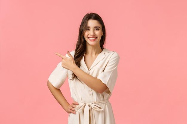 Entusiasmado positiva morena menina bonita vestido bonito, apontando o canto superior esquerdo, mostrando com prazer a promoção de descontos de produto, rosa de pé, sorrindo alegre e animado