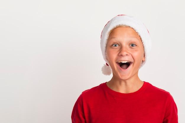 Entusiasmado rapaz usando chapéu de papai noel