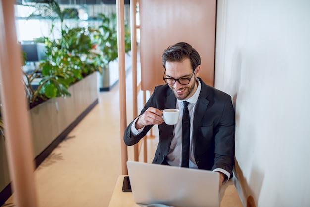 Entusiasta bonito caucasiano barbudo empresário de terno e óculos, sentado à mesa, bebendo café e terminando o relatório. interior da empresa.