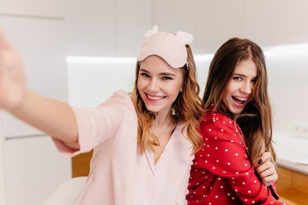 Entusiasta da menina branca em um maiô da moda, posando na sala iluminada com a irmã. retrato de modelo feminino encaracolado fazendo selfie a rir.