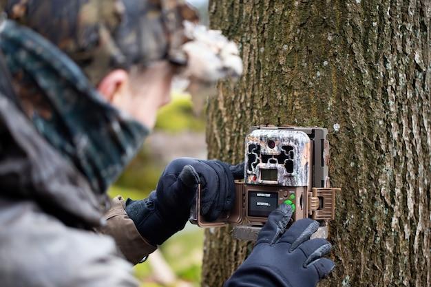 Entusiasta da vida selvagem montando uma câmera de trilha na árvore e operando botões