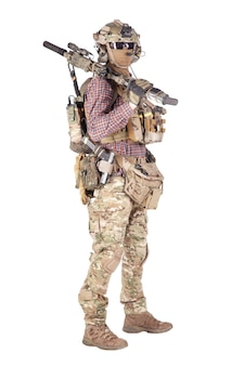 Entusiasta de strikeball com camisa quadriculada usando munição militar, máscara facial, capacete e fone de ouvido de rádio, óculos táticos, calças camufladas, rifle de serviço armado e arma de tiro em estúdio isolado no branco