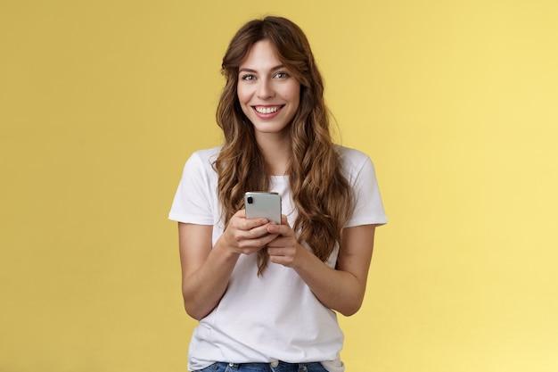 Entusiasta encantadora jovem sociável amiga de mensagens enviando fotos mídia social segurar smartphone câmera olhar felizmente amigável sorrindo suporte fundo amarelo roupa casual