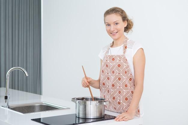 Entusiástico, atraente, dona de casa, mexendo, sopa, pote