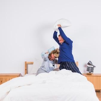 Envelhecido feliz mulher e homem com almofadas se divertindo na cama
