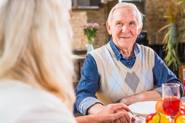 Envelhecido, homem sorridente, sentando, tabela