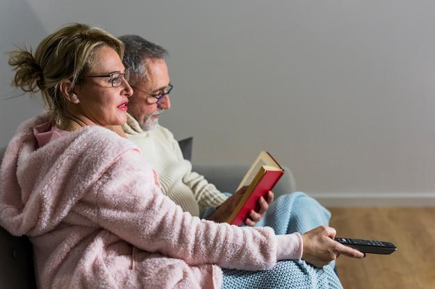 Envelhecido, mulher, com, controle remoto tv, observar, tv, e, leitura homem, livro, ligado, canapé