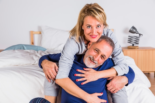 Envelhecido, mulher sorridente, abraçando, homem, perto, cama