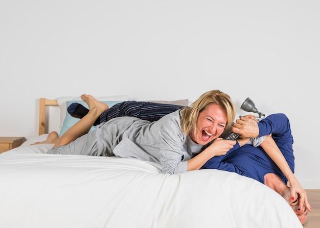 Envelhecido, rir, mulher, querer, tomar, tv remoto, de, homem, mãos, cama