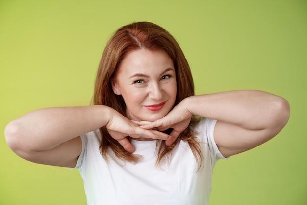 Envelhecimento cosmetologia, conceito de bem-estar, mulher ruiva feliz, auto-segura, de mãos dadas sob o queixo, sorrindo, mostrando manchas no rosto, rugas aceitas aplicando produtos para a pele parede verde