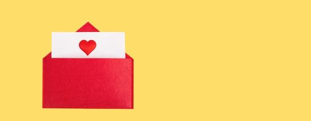 Envelope aberto banner vermelho com uma folha de papel com um coração em um fundo amarelo com copyspace. conceito de feriados do dia dos namorados e notas de amor