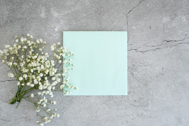 Envelope aberto com arranjos de flores no fundo rosa