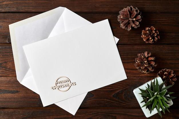 Envelope aberto com papel timbrado em branco sobre fundo de madeira com cones de mel e uma pequena planta em uma panela
