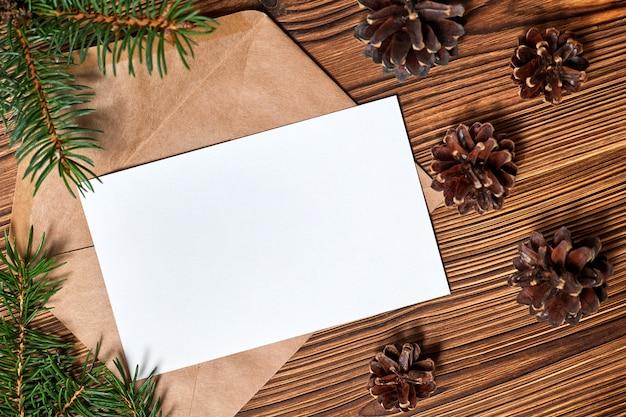 Envelope aberto com papel timbrado em branco sobre fundo de madeira com pinhas e ramos de abeto