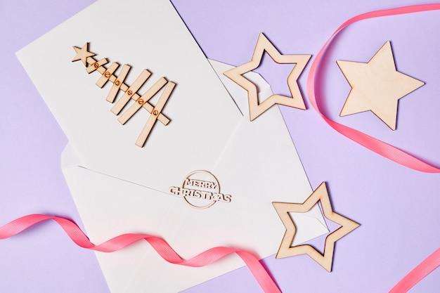 Envelope aberto com papel timbrado em branco sobre fundo roxo e acessórios de natal